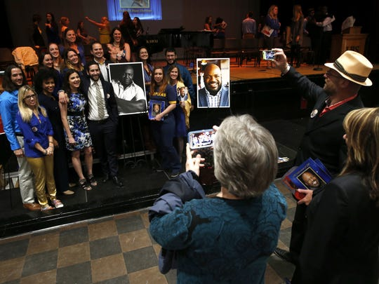 Current and former students of Rod Durham pose with memorial photos during a service held Monday at Leon High School, from where Durham graduated in 1982 and later went on to teach drama classes.