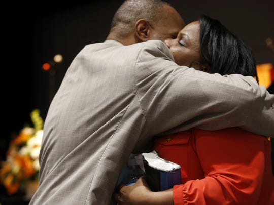 Marcellas Durham Jr. and Anika Daughtry, brother and cousin of Rod Durham, share a hug during his memorial service Monday at Leon High School, from where Rod graduated in 1982 and later went on to teach drama classes.