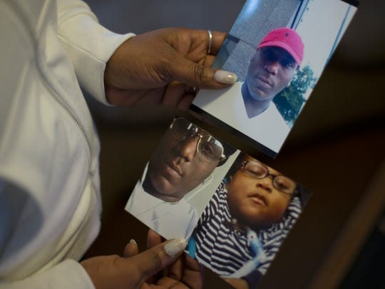 Kecia Bronson, mother of murder victim Justin Madaris, 21, poses with a photo of her son at her home in the Avondale neighborhood of Cincinnati, on Thursday, March 24, 2016.