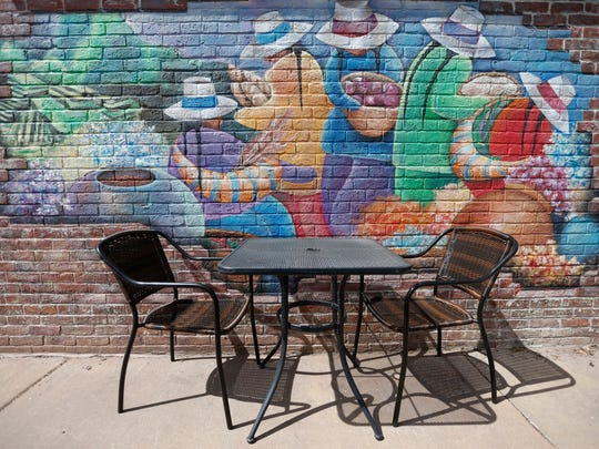 A mural decorates the brick wall on the patio at Cafe