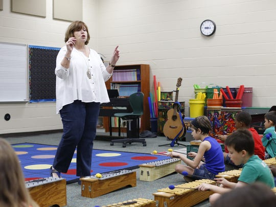 Carol Ann Mathews, a music teacher of 32 years, leads a music lesson at Kate Sullivan Elementary School. White is one of eight long-time school employees who retired last year.