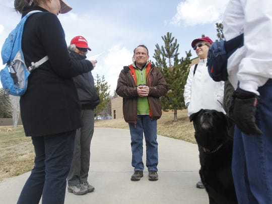 Ken Oros, center, joins a conversation on March 25 before a walk along the Animas River in Durango, Colo. Cancer survivors, patients and caregivers meet twice a month to walk along the river, which can improve both their physical and mental well-being.