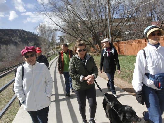 """Participants in a March 25 Live by Living """"Walk Along the River"""" event walk along the Animas River in Durango, Colo."""