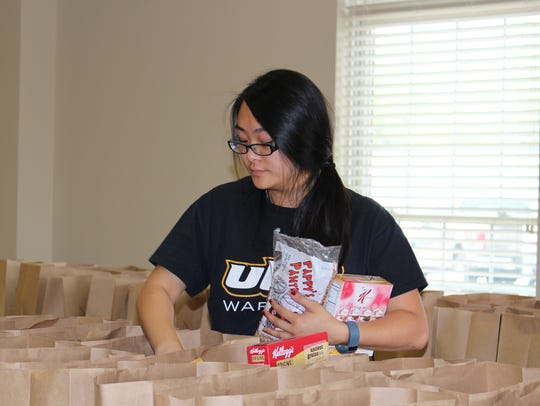 Hien Nguyen sorts products into donation bags at the
