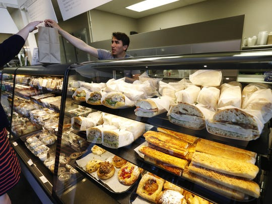 Freshly made sandwiches, breads and pastries sit behind the counter as customers order up lunch Thursday, April 14, 2016, at La Mie Express in downtown Des Moines.