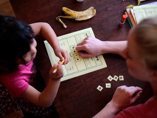Aya Hirose, 5, works with Becca Gasiewicz, 31, from