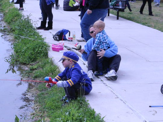 """Families fish at Glasgow Park Fishing Pond during the first """"Casting with Cops"""" on Saturday, April 30. The event paired county police with young anglers and kicked off the opening of the fishing pond."""