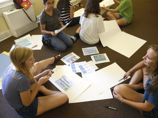 Molly Kennedy, clockwise from left, Jacqueline Cruz, and Grace Pickron, members of the First Presbyterian Church youth group, work to create signs Sunday during a planning session for a bone marrow registry planned for Saturday. The event was set up to help Kira Sullivan, 20, who has a rare condition of aplastic anemia.