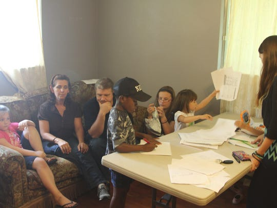 Bobbi and Bradley Eiler sit with their five adopted children and Bobbi's biological daughter, Casi Norris.