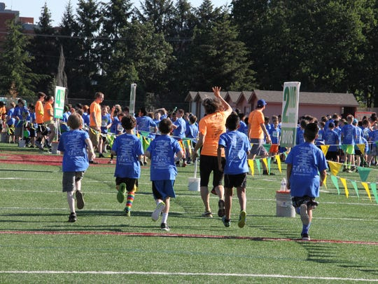 Fourth grade boys run out to the warm up area at Awesome 3000 on Saturday, May 7, 2016.