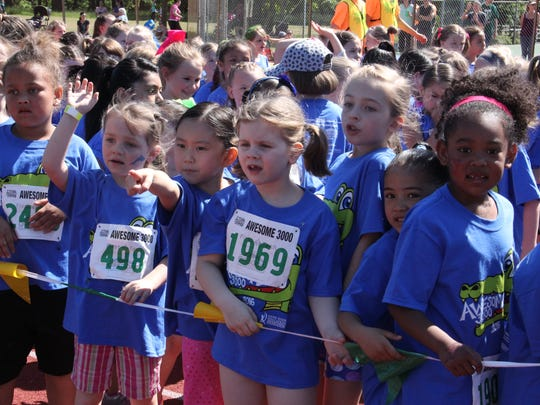First grade girls line up for the start of their run at Awesome 3000 on Saturday, May 7, 2016. They pointed and waved as they found their family in the crowd.