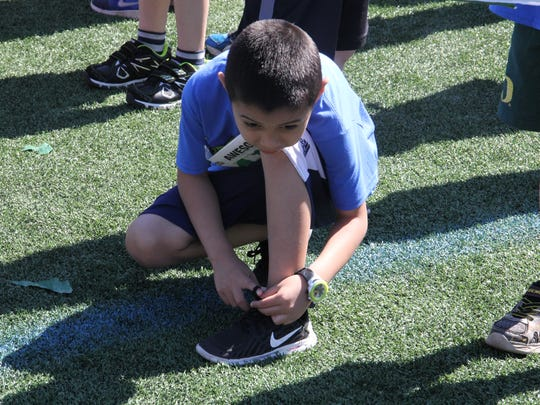 Xavi Ceja ties his shoes before his Awesome 3000 run on Saturday, May 7, 2016.