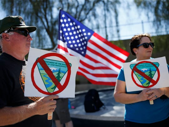 David Andersen, left, and Kaylene Andersen, of Overton, Nev., hold signs during a rally in support of rancher Cliven Bundy outside of the federal courthouse Friday, April 22, 2016, in Las Vegas. A U.S. magistrate judge is due to decide if trial will be held next month in Las Vegas for Bundy and 18 other defendants in an armed confrontation in Nevada with government agents two years ago.