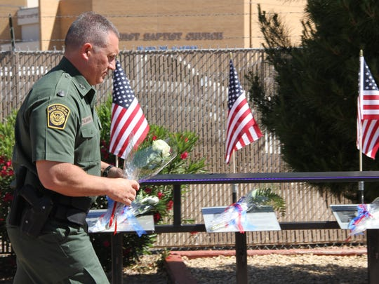 A member from the U.S. Customs and Border Protection Department lays a single white rose on a fallen officer's memorial from his department Wednesday morning.