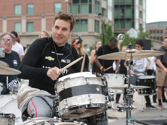 IndyCar driver Will Power beats the drums as 500 musicians