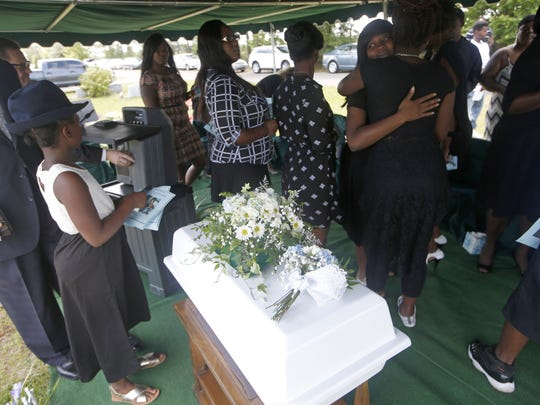 Tateyana Smith, right, hugs family and friends near the casket of her son, 10-month-old Jeffery Lamar Phillips III, at the Southside Cemetary where the infant will be laid to rest on Saturday, May 21, 2016.