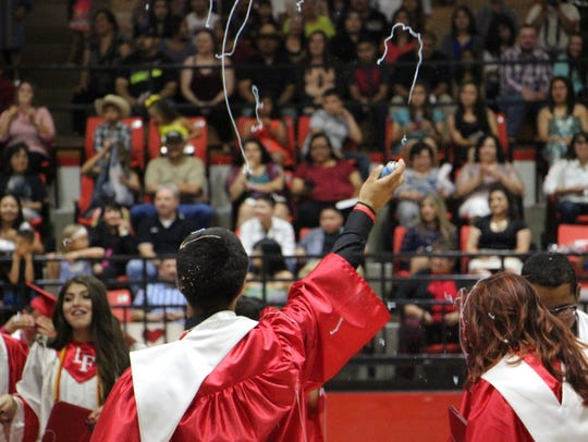 A newly graduated student shoots silly string.