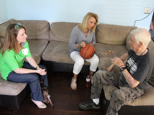 Alive Hospice social worker Lauren Goley watches as former professional basketball player Tiffany Woosley signs a ball for client Harvey Branch, one of her biggest fans. Branch and his daughter, Jennifer Frank, followed Woosley when she played for the nationally ranked Shelbyville Central High School Eaglettes in the 1990s.