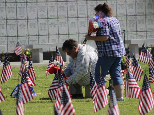 Fernley Mayor Roy Edginton lays flowers on his father's