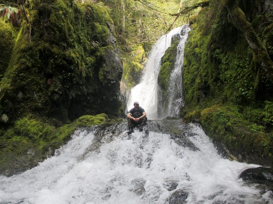 Jeff Green sits in the spray of Jackie Falls in the Family Falls system of waterfalls on upper Henline Creek.