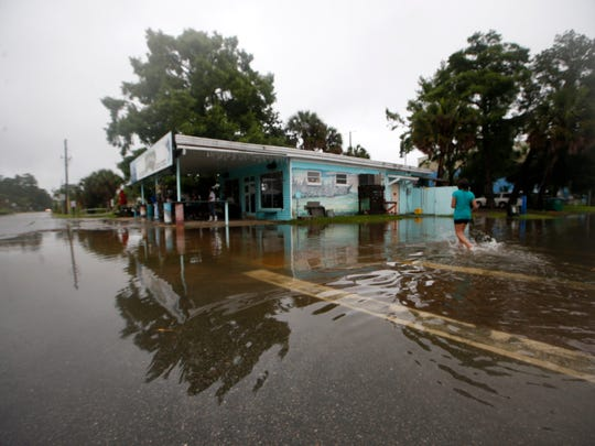 Residents walk through the flooded streets Monday in