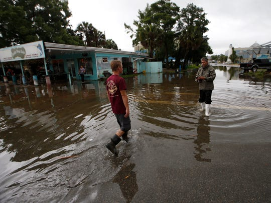 Residents walk through the flooded streets Monday in St. Marks of Wakulla County, one of 34 counties in the state declared in emergency by Gov. Scott based on the path of Tropical Storm Colin.
