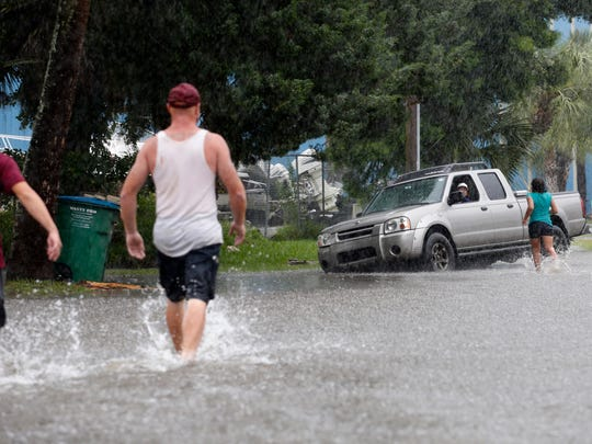 Residents walk through the flooded streets to help a driver who has driven into a ditch Monday in St. Marks of Wakulla County, one of 34 counties in the state declared in emergency by Gov. Scott based on the path of Tropical Storm Colin.