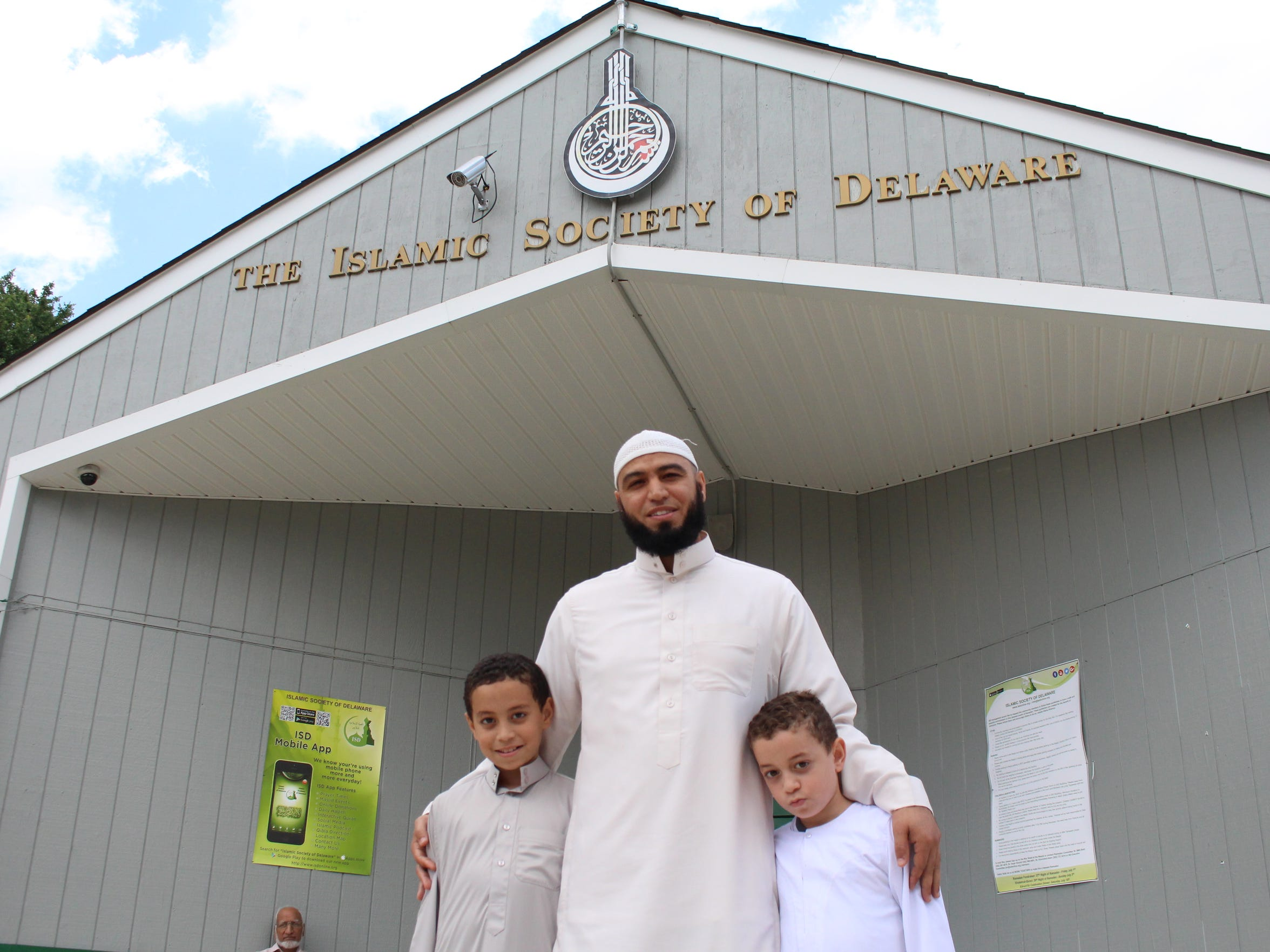Imam Sheikh Abdul Hadi  stands outside the Islamic Society of Delaware with his sons.