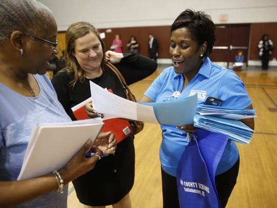 Katie Kone, center, accepts a contract to teach second grade at Apalachee Elementary School, from Principal Iris Wilson, left, and Leon County School's Assistant Director for Human Resources Deana McAllister, during a job fair at Chiles High School on Thursday. Nearly a quarter of the 112 elementary school jobs available had been filled one hour into the 8-hour job fair.