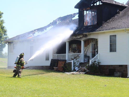 Crews work to extinguish the fire that engulfed a home