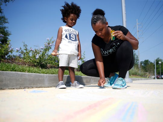 Jasmine Leslie and her son Javian Gonzalez, 2, create sidewalk chalk art along a stretch of the Capital Cascades Trail. Taking a walk outside and or playing with chalk are ways to release stress related to the coronavirus.