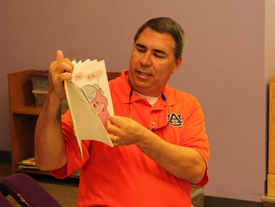 Matt Hall holds up a book and reads it to children