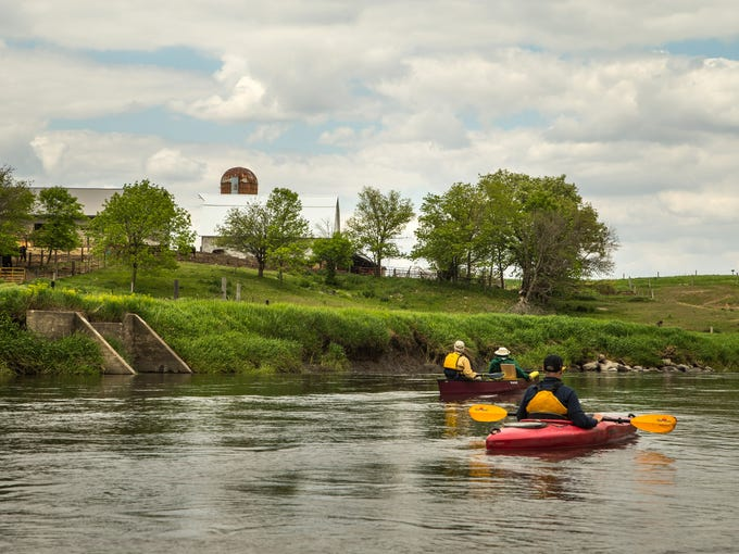 Rex Harvey and Steve Roe paddle past a farm as they