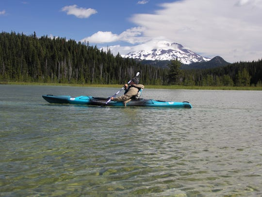 Matt Achor, of Minnesota, paddles the clear water of Hosmer Lake in Central Oregon.