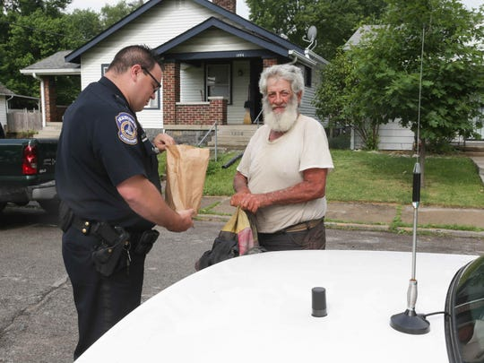 IMPD patrolman Adam Perkins, left, gives a bag of food to Kevin Wenning, a man living on the streets on the east side, Wednesday, June 15, 2016.