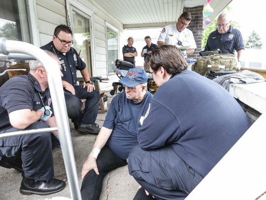 CORE paramedic Shane Hardwick, left, and IMPD patrolman Adam Perkins, right, respond to a 911 call for a fall by east-side resident Nicholas Fougerousse on Wednesday, June 15, 2016. By meeting with Fougerousse, representatives from the Shalom Project can help to direct him to services that can help him avoid future issues.