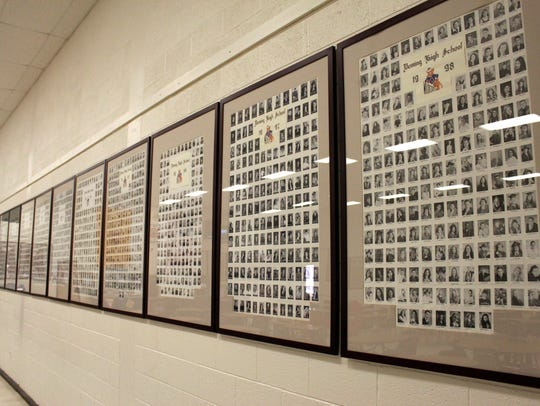Class photos from as early as 1901 line the walls of