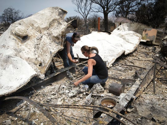 Douglas Nelson, left, shows his wife, Amy, an item he found as they survey the remains of their home devastated by a wildfire, Saturday, June 25, 2016, in South Lake, Calif.