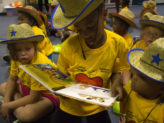 Kennedy Fuller, 7, reads to some friends from her new