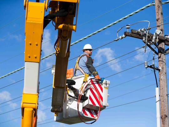 Dave Bennett works on a power line on Aug. 13 in New