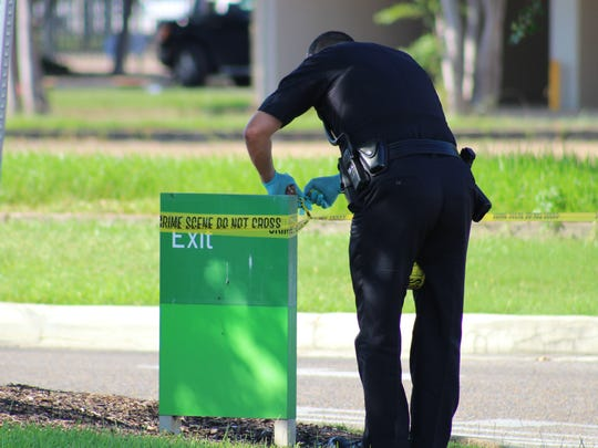 An Alexandria Police Department officer posts crime scene tape at an entrance to the downtown Alexandria Regions Bank branch with crime scene tape after it was robbed on Friday afternoon.