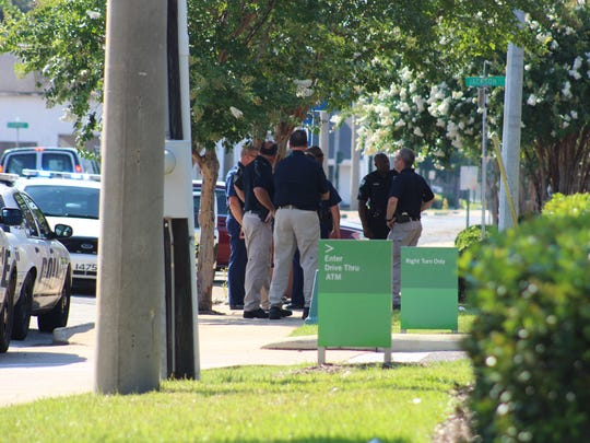 Alexandria Police Department Chief Loren Lampert (right) stands with other members of the department on Friday afternoon outside of the Regions Bank branch, which earlier had been robbed.