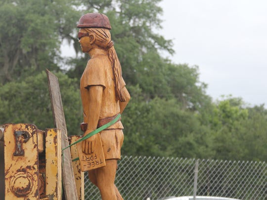 The girl character in Birch's wood carving waits to