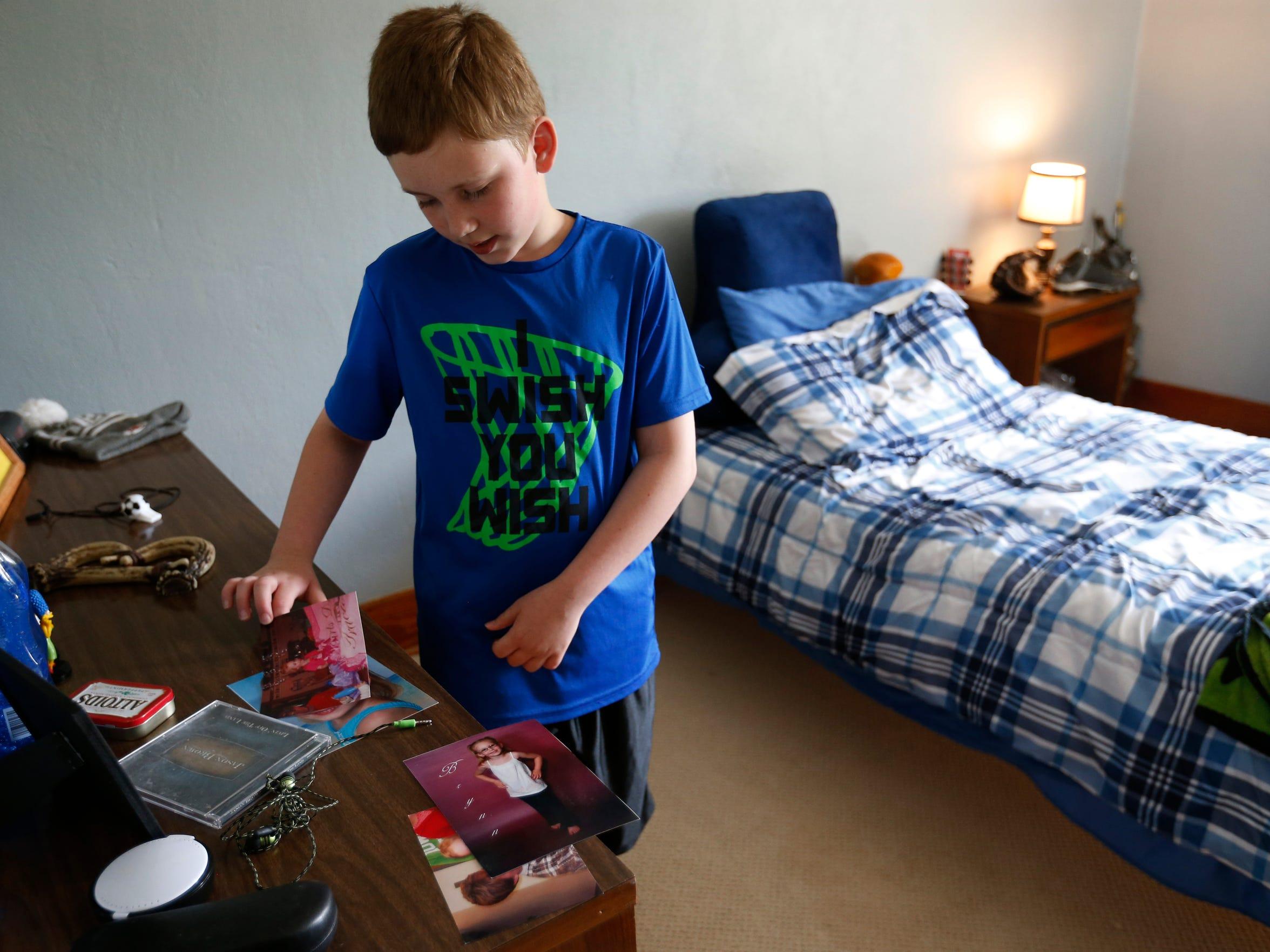 Bryan Brown, 10, looks at photos of him as Brynn at