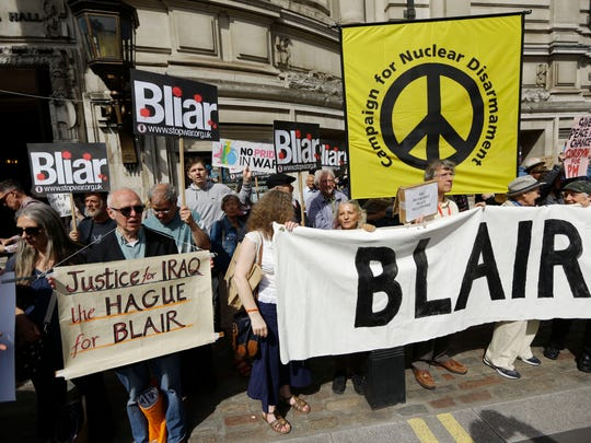 Protesters hold placards outside the Queen Elizabeth II Conference Centre in London, shortly before the publication of the Chilcot report into the Iraq war, Wednesday, July 6, 2016. Thirteen years after British troops marched into Iraq and seven years after they left a country that's still mired in violence, a mammoth official report is about to address the lingering question: What went wrong? On Wednesday, retired civil servant John Chilcot will publish his long-delayed, 2.6 million-word report on the divisive war and its chaotic aftermath.