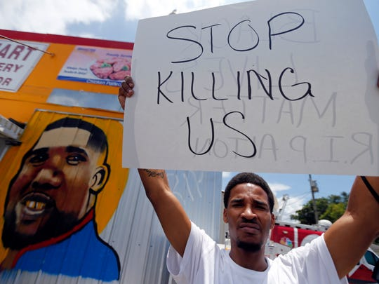 A man holds a sign in front of a mural of Alton Sterling while attorneys, not pictured, speak in front of the Triple S Food Mart in Baton Rouge, La., Thursday, July 7, 2016. Sterling, 37, was shot and killed outside the convenience store by Baton Rouge police, where he was selling CDs.
