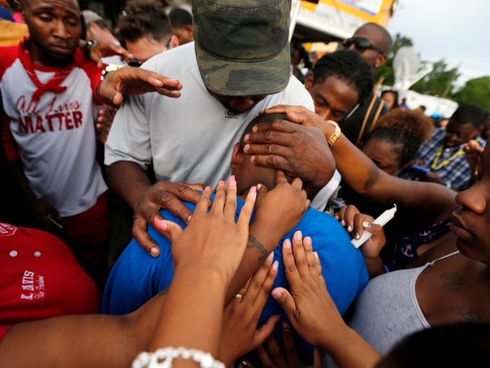 Cameron Sterling, son of Alton Sterling, is comforted