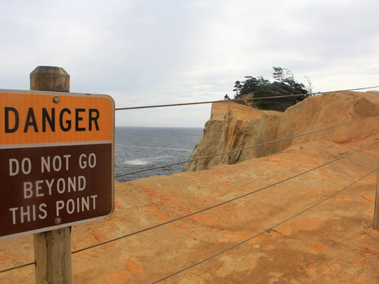 Signs warn people not to travel out on the sandstone bluff at Cape Kiwanda on the Oregon Coast.