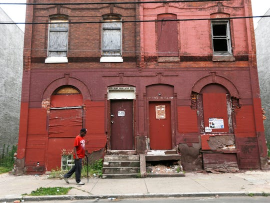A man walks through a blighted neighborhood in Philadelphia in 2013. Democrats are set to begin their convention at the end of July in a city that symbolizes both the nation's promise and its shortcomings.