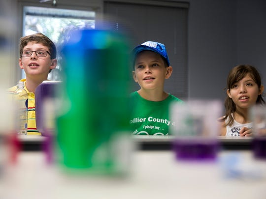 Tom Mitchell of Chicago, from left, Jake Norton of Lake Worth, Fla., and Jolette Gurrola of Naples watch carefully during a PH balance experiment at the Collier County Fairgrounds during the Southwest Florida Weather Camp Friday, July 15, 2016 in Naples, Fla. The experiment allowed campers to see first hand how acidic household products are.